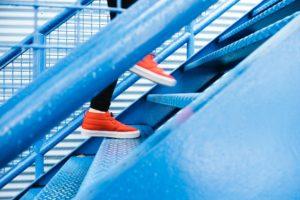 red shoed feet walking up blue metal staircase