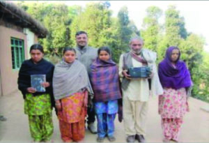 Indian Family standing outside man holding radio