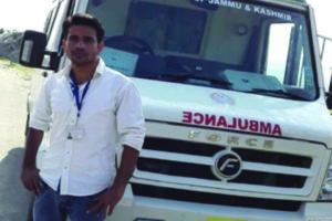 Young indian man posing in front of ambulance