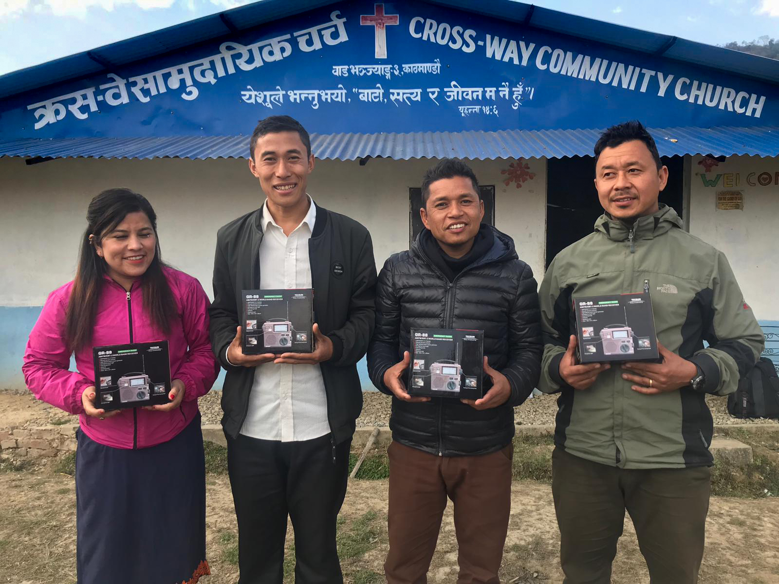 Four Nepali people standing outside church holding radios