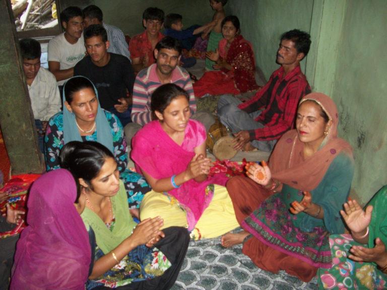 group of woman sitting on floor singing