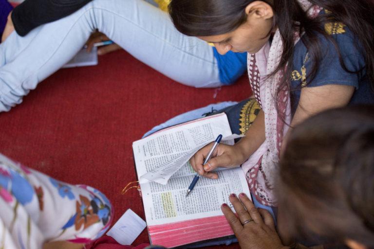 woman writing in Bible