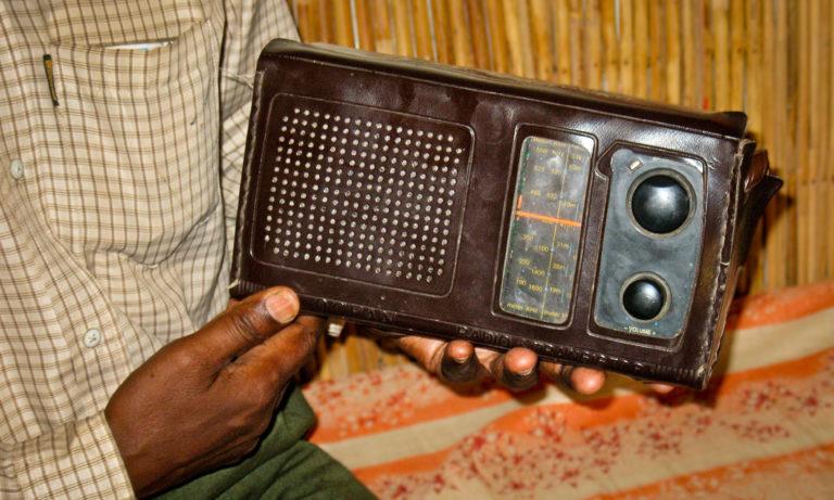 hands holding old radio