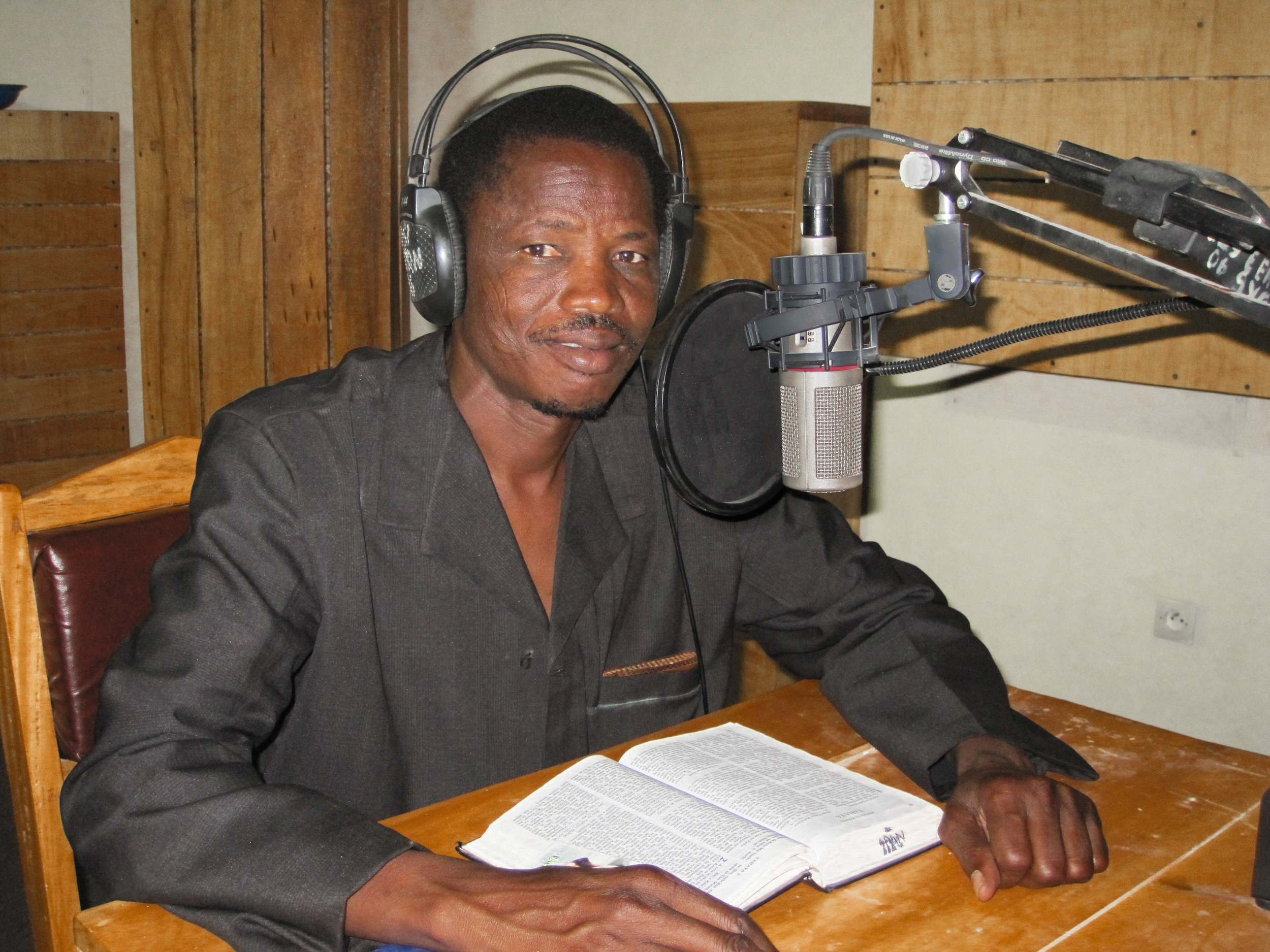 Niger man with headphones recording at microphone