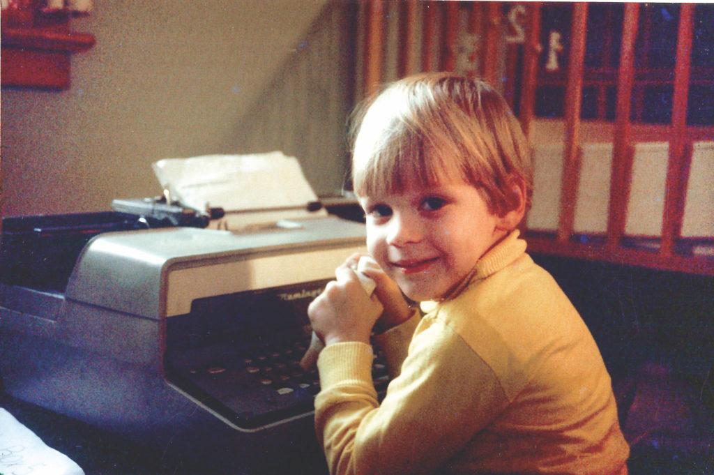 Steven Laman as a boy using typewriter