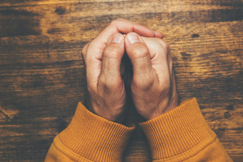 top view of male crossed hands in prayer
