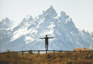 Individual standing on fence by mountains raising arms