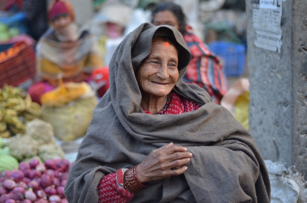 smiling indian woman with headcovering at outdoor market