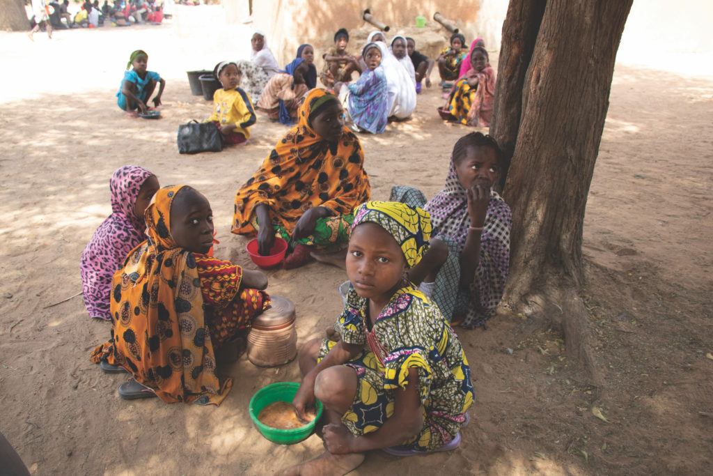 african children sitting under tree eating a meal