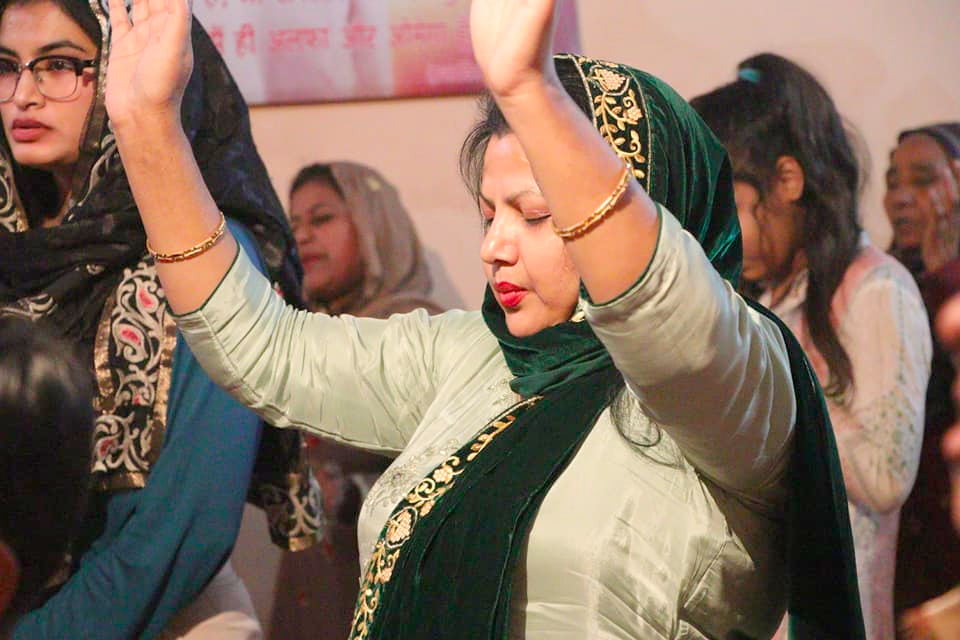indian woman in church worshipping with raised hands